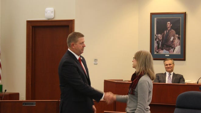 Madeira Police Chief David Schaefer, left, shakes hands with Mayor Melisa Adrien after being sworn in as the new police chief.