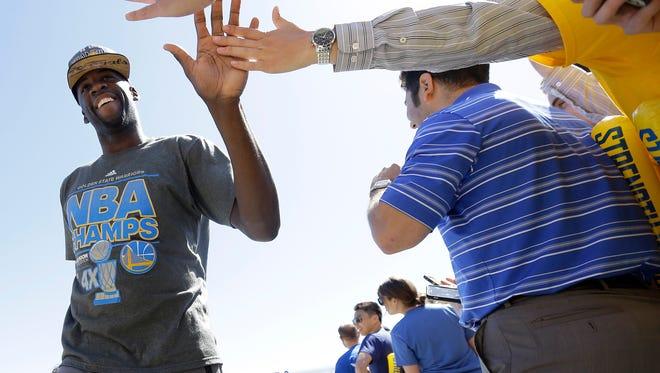 Golden State Warriors forward Draymond Green, left, high-fives team employees after landing in Oakland, Calif., on Wednesday, June 17, 2015.