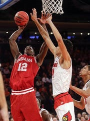 Indiana's Hanner Mosquera-Perea (12) drives past Louisville's Anas Mahmoud (14) during the first half of an NCAA college basketball game Tuesday, Dec. 9, 2014, in New York.