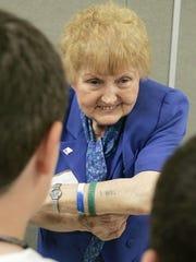 Holocaust survivor Eva Kor shows students the tattoo