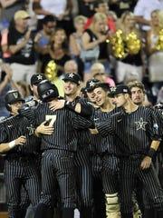 Vanderbilt players celebrate as Dansby Swanson (7) scores.