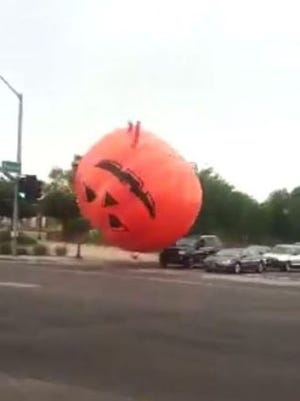 A large, inflatable pumpkin was captured on video bouncing through a Peoria, Ariz., intersection on Thursday, Oct. 29, 2015. Strong wind gusts blew it away from a Halloween display.