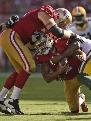 San Francisco quarterback Colin Kaepernick ended up on the ground on this play against the Packers, but he's been in the air frequently this season. A website says his 49ers will travel almost 14,000 miles this year, most in the National Football League.