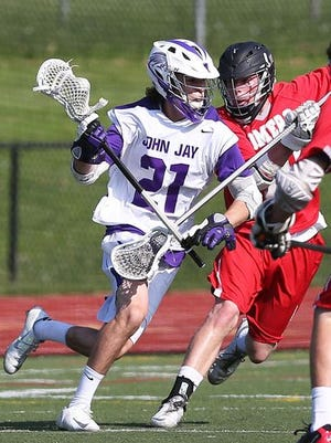 From left, John Jay's Matt Lupinacci (21) tries to get around Somers' Evan Kieltyka (10) during playoff lacrosse action at John Jay High School in Cross River May 19, 2015. John Jay won the game 12-5.