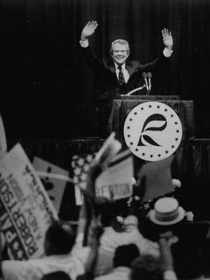 "Republican presidential candidate Pat Robertson waves to supporters during the 1987 ""Cavalcade of Stars"" straw poll in Ames. Robertson's victory in the straw poll was one of the earliest indications of Christian conservatives' political influence in Iowa."
