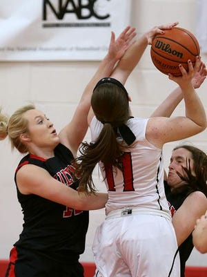 Hilton's Cameron Graupman defends Penfield's Emma Guy in Tuesday's Monroe County matchup won 58-56 in overtime by the Patriots.
