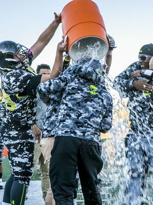 Diamond Ranch players celebrate winning the 1A football title by giving their coaches a nice cold bath.