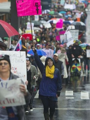 Christine Ball-Blakely walks up Locust Street in downtown Knoxville during the Women's March on Saturday, Jan. 21, 2017. Over 2,000 people participated in the march despite rain.
