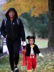 Amya Millsap, 13, and Kai Douglas, 2, go trick-or-treating in Des Moines on Beggars NIght Monday, Oct. 30, 2017.