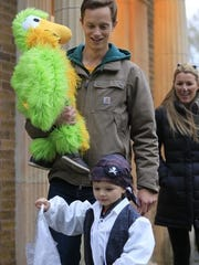 Tait Sand, 4, dressed as a pirate and Axel Sand, 1, dressed as a parrot go trick-or-treating with their father Rob Sand and aunt Kelly Lauridsen Monday, Oct. 30.