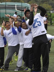 Theo Riddick takes a selfie with kids during a football clinic on Tuesday.