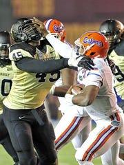 Florida quarterback Treon Harris (3) stiff-arms Vanderbilt's