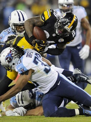Pittsburgh Steelers running back Le'Veon Bell (26) is tackled by Tennessee Titans safety Michael Griffin (33) and Avery Williamson during the first quarter at LP Field.