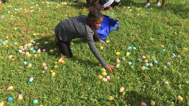 Kaidence Kimbrough, 8, collects Easter eggs Saturday at Astoria Elementary School.