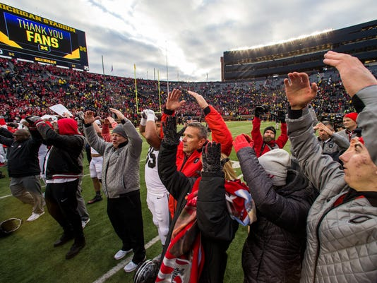 Ohio State head coach Urban Meyer, center, sings with his team and family members on the Michigan Stadium field after an NCAA college football game against Michigan in Ann Arbor, Mich., Saturday, Nov. 25, 2017. Ohio State won 31-20. (AP Photo/Tony Ding)