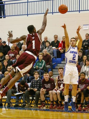 Catholic Central's David Weber (2) launches a jumper over U-D Jesuit's 6-foot-9 Ikechukwu Eke during Tuesday's game.