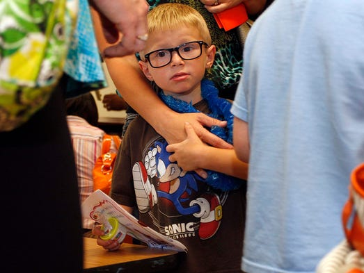 Student Connor Patrick anxiously waits in his new classroom during Kindergarten orientation at Sherwood elementary school in west Springfield on August 11, 2014.