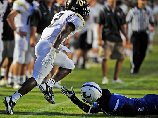 Lebanon's Marqualis Williams, right, looses his helmet after pushing Mt. Juliet's Kyle Smith out of bounds during the first half in Lebanon, Tenn., Thursday, Aug. 22, 2013.