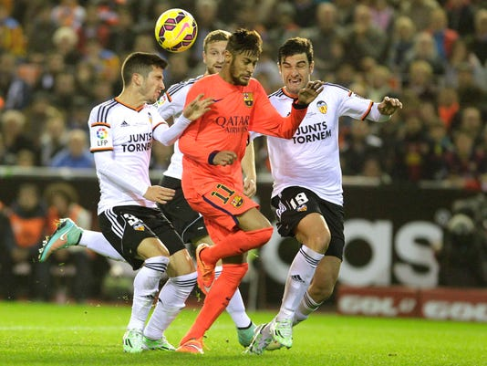 Barcelona's Neymar fights for the ball against Valencia's Gaya, Mustafi and Barragan during their Spanish first division soccer match at the Mestalla stadium in Valencia