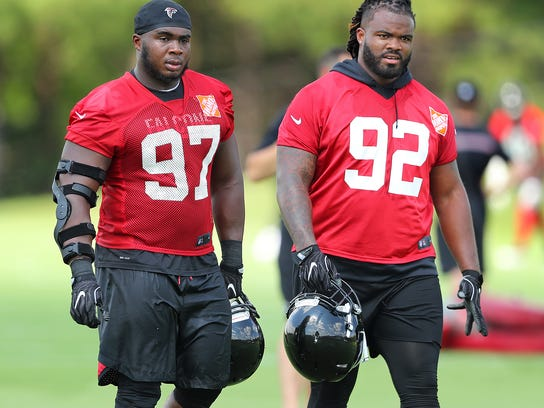 Atlanta Falcons defensive tackles Dontari Poe (92) and Grady Jarrett walk off the field after NFL football practice Tuesday, June 13, 2017, in Flowery Branch, Ga. (Curtis Compton/Atlanta Journal-Constitution via AP)