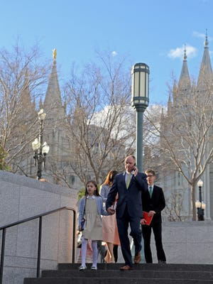 Members of The Church of Jesus Christ of Latter-day Saints gather Sunday morning across the street from Temple Square in Salt Lake City.