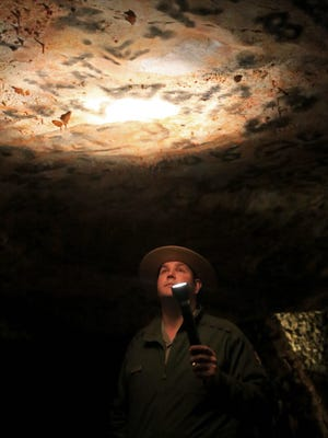 """Ranger Andrew Young shines a flashlight on the """"ceiling"""" of the Inscription Room at Lehman Caves to show the historic graffiti left behind by early cave visitors at what is now Great Basin National Park in Nevada."""