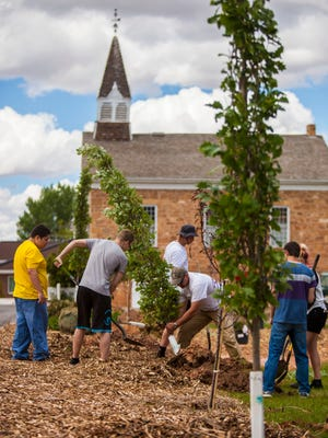 Students plant trees at the city's war memorial during the school's cleanup day in Parowan, Wednesday, May 18, 2016.