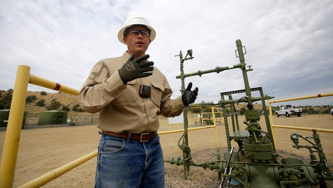 ConocoPhillips optimization technician Jamie Huffman talks on June 30 during a tour of a ConocoPhillips natural gas site in Aztec. The company is touting its environmental programs to cut methane emissions.