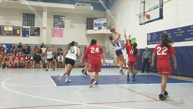 Academy's Mia San Nicolas shoots over defenders for an easy bucket in the paint.