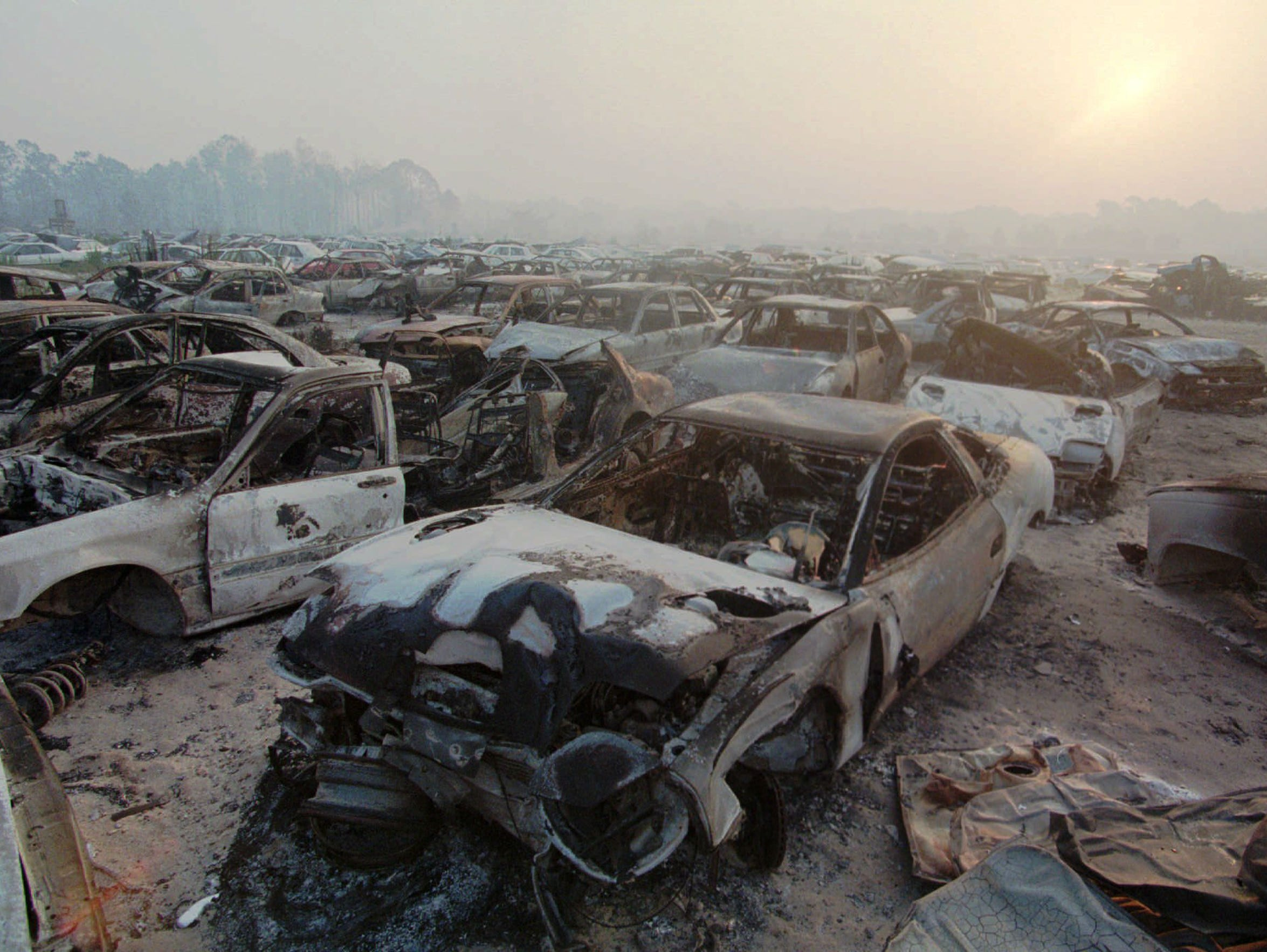 Burned cars litter an auto salvage company in Mims