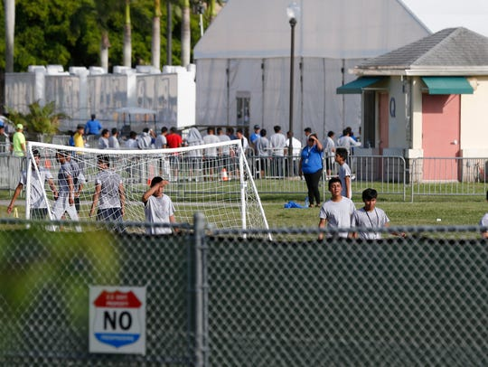 Immigrant children play outside a former Job Corps