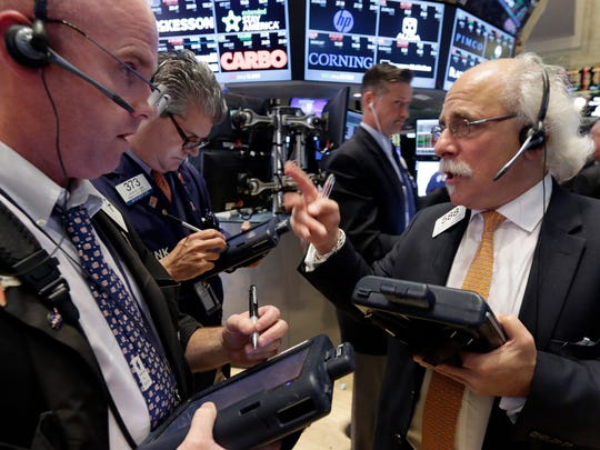 Traders Kevin Walsh, left, and Peter Tuchman, right, confer as they work on the floor of the New York Stock Exchange Tuesday.