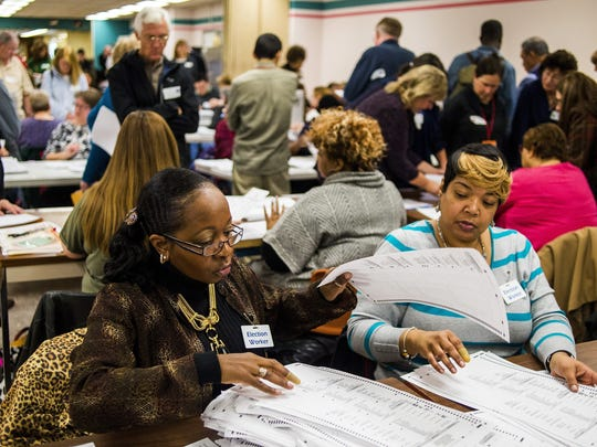 Election workers recount votes on Flint ballots, as they begin the process of a statewide recount on Wednesday, Dec. 7, 2016 at Genesee County Administration Building in Flint, Mich. A federal judge could decide whether to end Michigan's presidential recount after the state's second-highest court said the Green Party nominee was ineligible to seek a second look at millions of ballots.   (Jake May/The Flint Journal-MLive.com via AP)