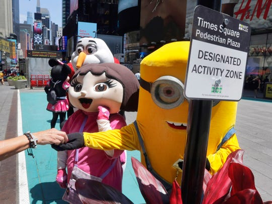 FILE - This June 21, 2016 file photo shows costumed characters working in a color-coded designated activity zone in New York's Times Square. Street performers and costumed characters can be issued summonses or face arrest if they're caught operating outside the eight designated rectangles, under new rules aimed at controlling overly aggressive street performers. Each area is painted teal and measures 8 feet by 50 feet.