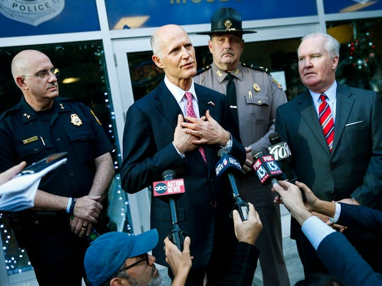 Florida Gov. Rick Scott, center, with Tampa Police Chief Brian Dugan, left, and Tampa Mayor Bob Buckhorn, right, talks with members of the media at Tampa Police Headquarters in Tampa, Fla., Wednesday, Nov. 29, 2017. Scott's visit followed the announcement of the arrest in the Seminole Heights murders.