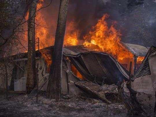A house burns near Casitas Pass Road as the Thomas