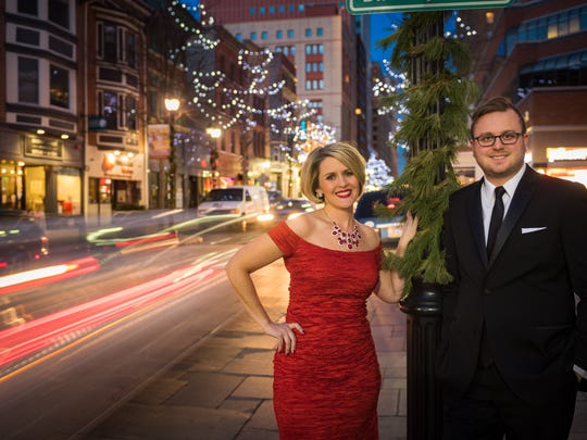 Amy Watson Bish in a Alex Evenings red formal gown from Macy's and Andrew Truscott in Suit #120 from Collars and Cuffs dodging holiday traffic on Market Street / Special To The News Journal, Joe del Tufo, Moonloop Photography / Special To The News Journal, Joe del Tufo, Moonloop Photography