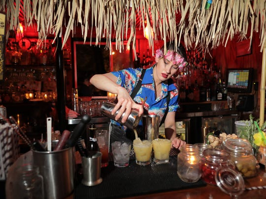 Larissa Hoffend pours a drink at a tiki party during