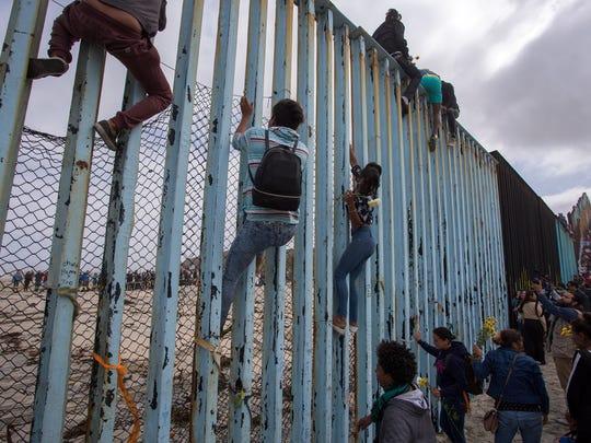 Migrantes escalan la cerca fronteriza de Tijuana.