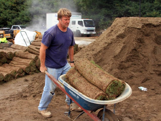 Rich Fancher of Home Green Advantage in Armonk carries sod to the new golf greens at Mark Stagg's home in Purchase.