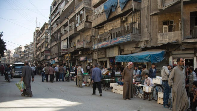 Syrian residents of the rebel-held side of the northern city of Aleppo shop on a street on Oct. 27, 2016.