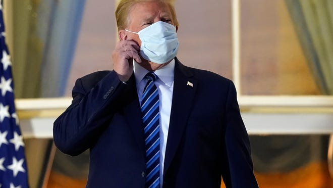 President Donald Trump removes his mask as he stands on the balcony outside of the Blue Room as returns to the White House Monday, Oct. 5, 2020, in Washington, after leaving Walter Reed National Military Medical Center, in Bethesda, Md. Trump announced he tested positive for COVID-19 on Oct. 2.
