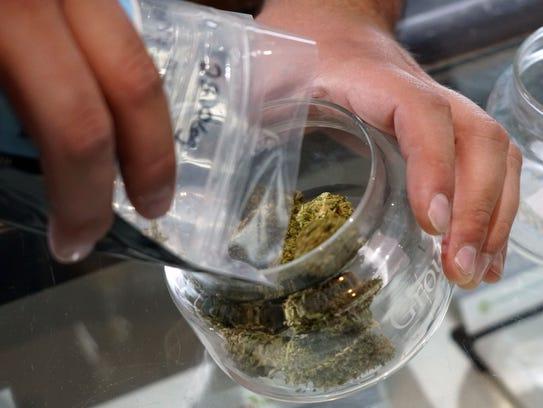 Budtender Tyler Schneckenberger pours marijuana into