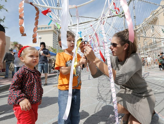 Kendra Martin ties ribbons on an art installation with