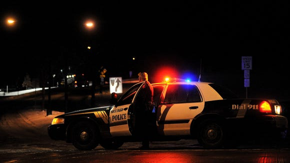 Law enforcement on scene along Cliff Avenue at the entrance to Tuthill Park in Sioux Falls, S.D., early Friday morning, Jan. 2, 2015, looking for a suspect who reportedly fired two shots at an officer.