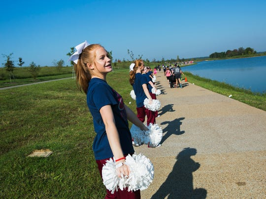 """September 16, 2017 - Callie Thomas, 14, a member of the Collierville High School Varsity Cheer, encourages runners as they participate in a 5k run during West Cancer Clinic's """"West Fight On: Cycle. Run. Walk."""" event at Shelby Farms Park on Saturday morning. The fundraising event will support The University of Tennessee/West Institute for Cancer Research, the non-profit fundraising arm of West Cancer Center. In addition to the 5k run, the event included a one-mile Tribute Walk and cycling routes at three distances."""
