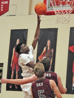 Copan High School's Correll Record powers to the basket, while two Oklahoma Union jayvee players attempt in vain to defend, during boys varsity basketball action last winter. Mike Tupa/Examiner-Enterprise