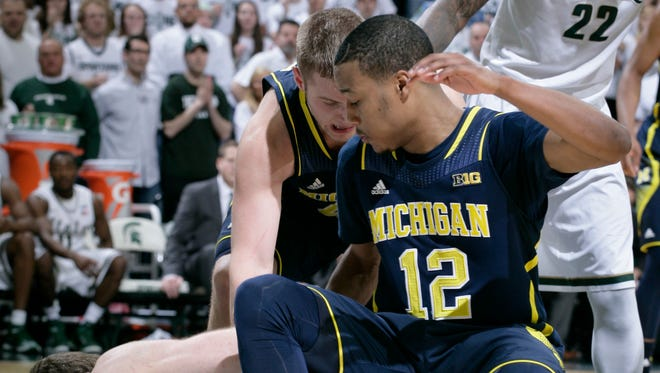 Michigan State's Matt Costello and Michigan's Muhammad-Ali Abdur-Rahkman (12) wrestle for the ball during overtime Sunday, Feb. 1, 2015, in East Lansing.