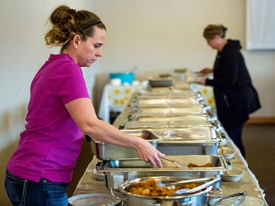 An employee refills food at the buffet during the fish fry at the RiverEdge Golf Course  in Marshfield, Wis., Friday, March 30, 2018.