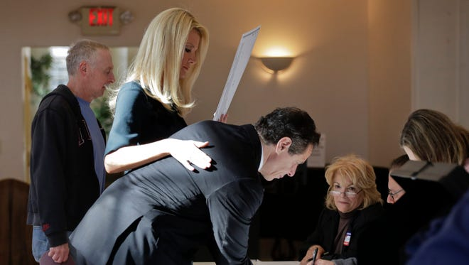 New York Gov. Andrew Cuomo signs in to vote along with his partner Sandra Lee, Tuesday in Mount Kisco.